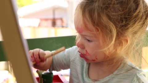 a young girl concentrating and painting on a easel. - ethnicity stock videos & royalty-free footage