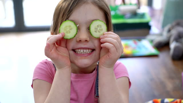 young girl covering eyes with cucumber - children only stock videos & royalty-free footage