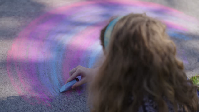 cu young girl creates a rainbow using chalk on the driveway - spectrum stock videos & royalty-free footage