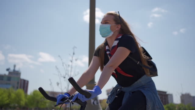 young girl cycling alone by the city waterfront, applying all measures of protection and social distance during a pandemic - slow-motion stock videos & royalty-free footage