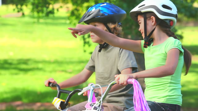 Young girl cycling with her brother / Cape Town, Western Cape, South Africa
