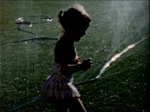 a young girl dances and plays in a sprinkler. - 1958 stock videos & royalty-free footage