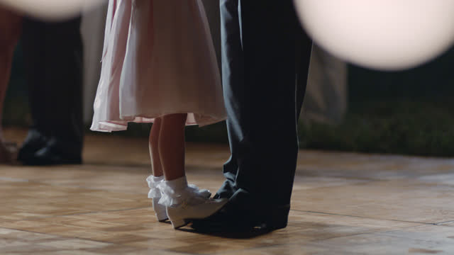 Young girl dances on her father's feet under twinkling lights at wedding reception.