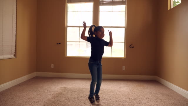 vídeos y material grabado en eventos de stock de ms young girl dancing in empty room of new house during move - zoom hacia dentro