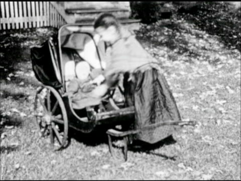young girl, daughter, placing cloth doll into carriage. woman handing high-chair, butter churn & plank to male hands inside conestoga covered wagon. - westward expansion stock videos & royalty-free footage