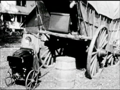 young girl, daughter pulling doll carriage up to wagon, male, father placing into conestoga covered wagon. - westward expansion stock videos & royalty-free footage