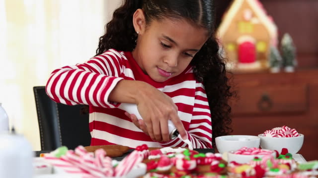 ms tu young girl decorating gingerbread cookies in kitchen / richmond, virginia, usa - decorating stock videos & royalty-free footage