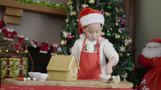 junges mädchen schmücken lebkuchenhaus für weihnachten zu feiern - weihnachtsmütze stock-videos und b-roll-filmmaterial