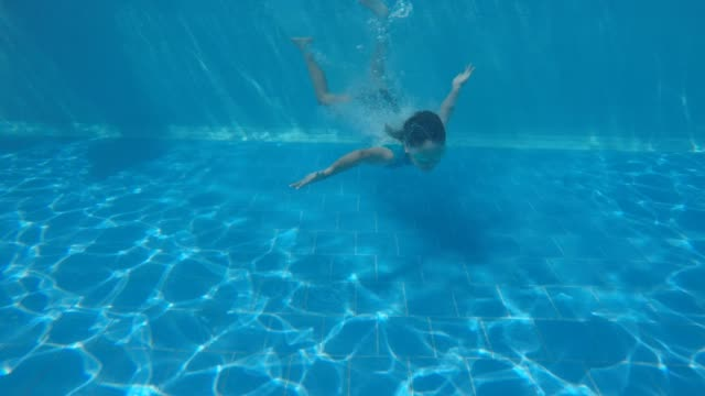 Young girl diving into a resort pool
