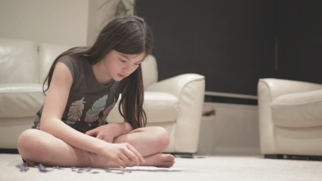 young girl doing a 3d puzzle in a living room - girl sitting cross legged stock videos & royalty-free footage