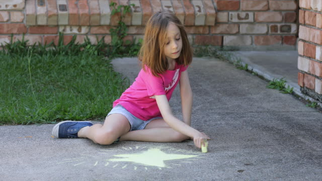 young girl doing chalk art on driveway - chalk art equipment stock videos & royalty-free footage