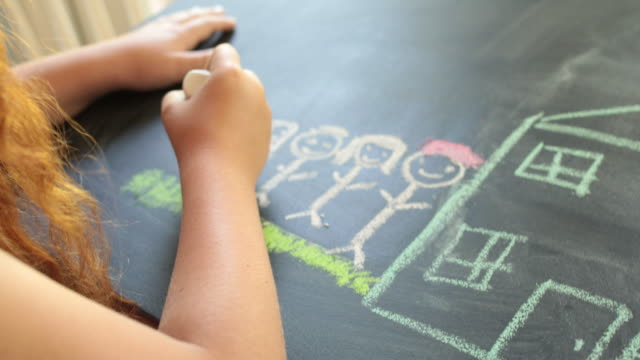 stockvideo's en b-roll-footage met young girl drawing a house and family with chalk on a table, over shoulder view - schoolbord