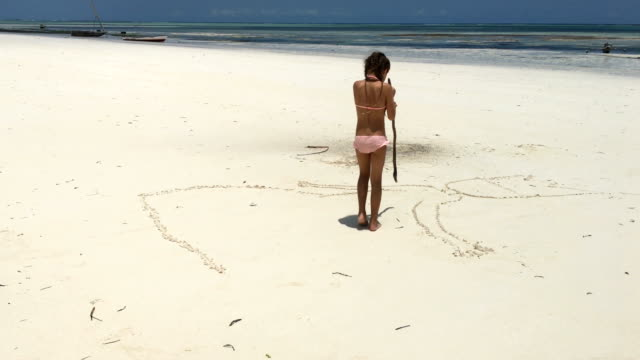 Young Girl Drawing in Sand on Beach of Tropical Island