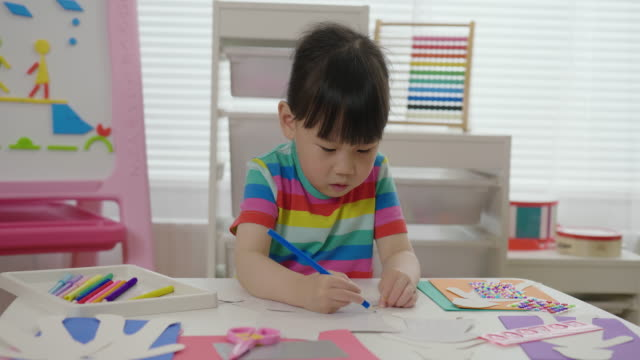 young girl drawing patterns for makes paper craft for home schooling - film moving image stock videos & royalty-free footage