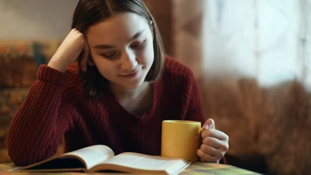 vídeos de stock e filmes b-roll de young girl drinking a cup of tea or coffee and reading a book - teenage girls