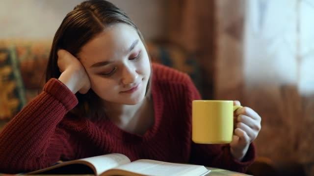vídeos de stock, filmes e b-roll de rapariga que bebe um copo do chá ou do café e que lê um livro - café bebida