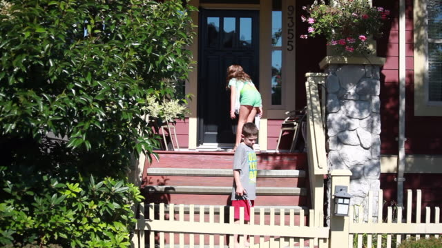 vidéos et rushes de young girl drops newspaper at the front door of a house, then walks down the stairs to meet a young boy who is holding scissors which he hands to the young girl on a sunny spring day - kelly mason videos