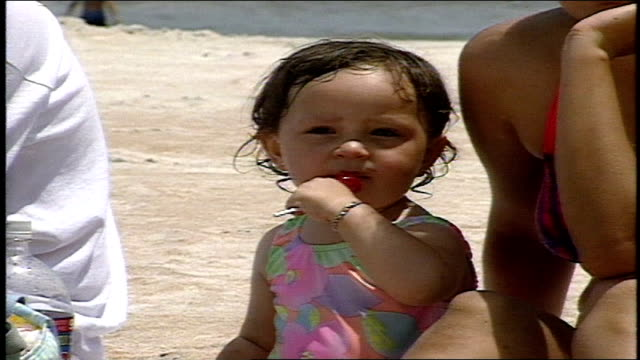 young girl eating a lollipop on beach next to parents in daytona florida - lollipop stock videos & royalty-free footage