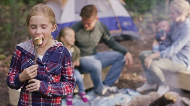 young girl eating a marshmallow in campsite - marshmallow video stock e b–roll