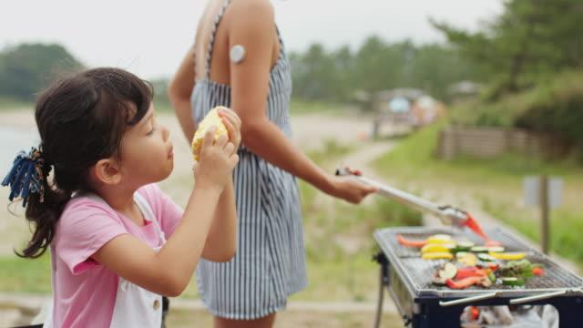 vidéos et rushes de jeune fille mangeant le maïs - activité de plein air