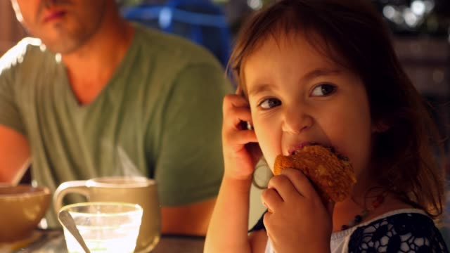 ms young girl eating muffin while sitting at table for breakfast with family - muffin stock videos and b-roll footage