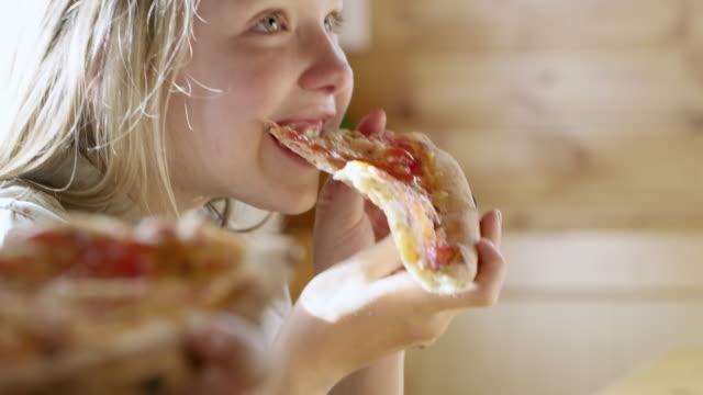 ms 少女のピザのスライスを食べる - unhealthy eating点の映像素材/bロール