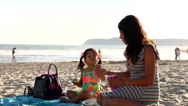 vídeos de stock, filmes e b-roll de ms young girl eating vegetables with mother while sitting on beach on summer evening - bolsa objeto manufaturado