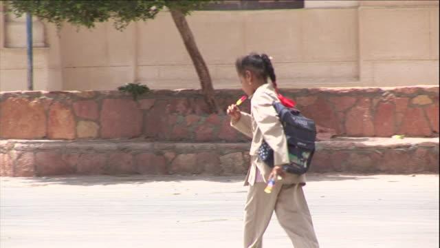 vídeos y material grabado en eventos de stock de a young girl eats an ice pop as she walks down a street. - rucksack
