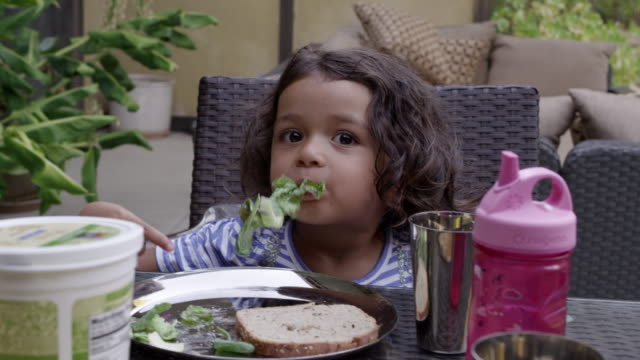 vídeos de stock e filmes b-roll de young girl eats her salad at dinner time in backyard dining table. - comida e bebida