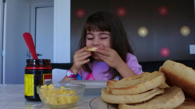 Young girl eats muffin splits