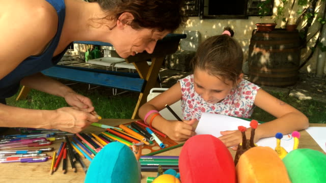 young girl enjoying drawing outdoors while mother assists her - art and craft stock videos & royalty-free footage
