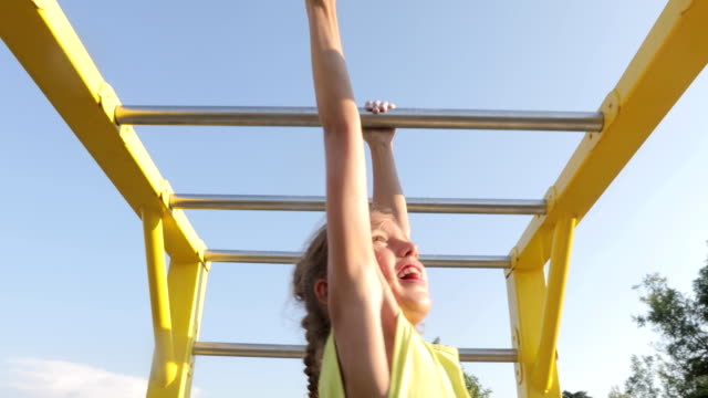 young girl enjoying exercising and playing outdoors - horizontal bar stock videos and b-roll footage