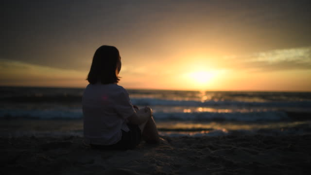 young girl enjoying sunset on the beach - sunset stock videos & royalty-free footage