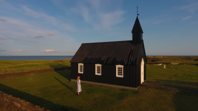 a young girl explores a black church in iceland. fairytale fashion story - christianity stock videos & royalty-free footage