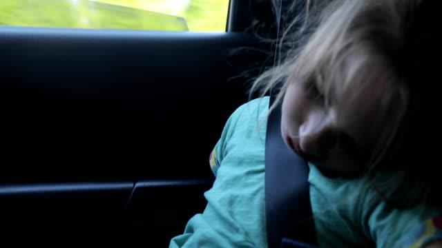 stockvideo's en b-roll-footage met jong meisje vallen in slaap in de auto terwijl traveling - veiligheidsgordel