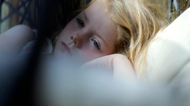 vídeos de stock e filmes b-roll de young girl falling asleep in the porch swing - só uma rapariga