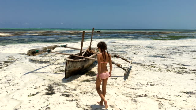 Young Girl Finding a Wooden Catamaran on Sandy Beach on Tropical Island