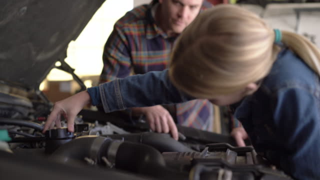 CU Young girl fixing a car's engine with her dad