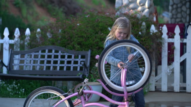 ms young girl fixing her bicycle by herself - repairing stock videos & royalty-free footage