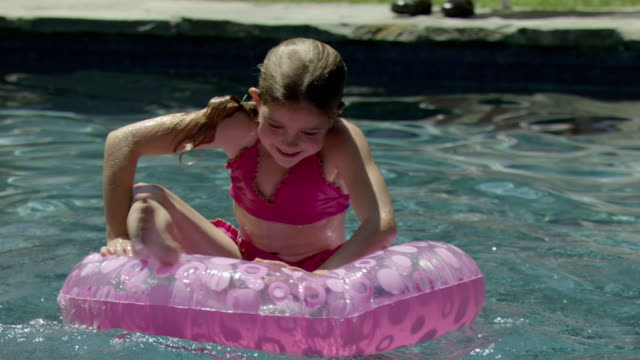 a young girl floats in an inner tube in a swimming pool. - inner tube stock videos and b-roll footage
