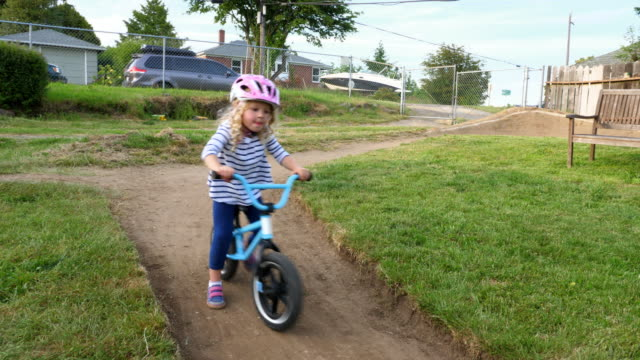 pan young girl following friend around dirt track while riding bicycles in backyard on summer afternoon - 挑戦点の映像素材/bロール