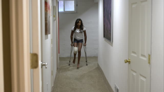 Young girl going down hallway on crutches.