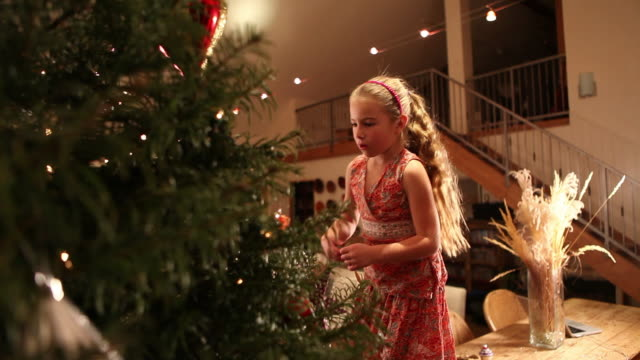 ms young girl hanging christmas ornaments on tree / lamy, new mexico, united states - lamy new mexico stock videos and b-roll footage