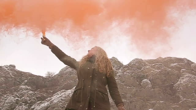 Young girl have fun with orange color smoke bomb
