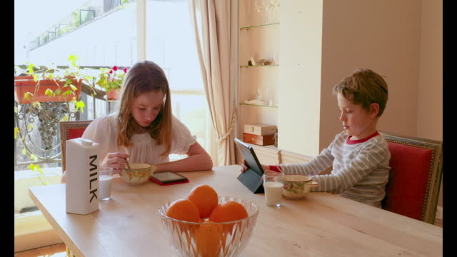 a young girl having breakfast with her digital tablet, morning - carton stock videos & royalty-free footage