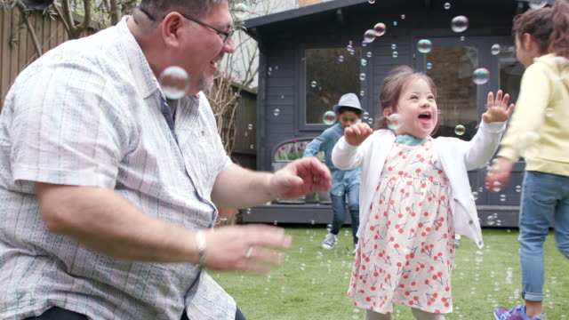 young girl having fun in the garden with her family - disability stock videos & royalty-free footage