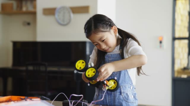 Young girl having fun working on a robot design