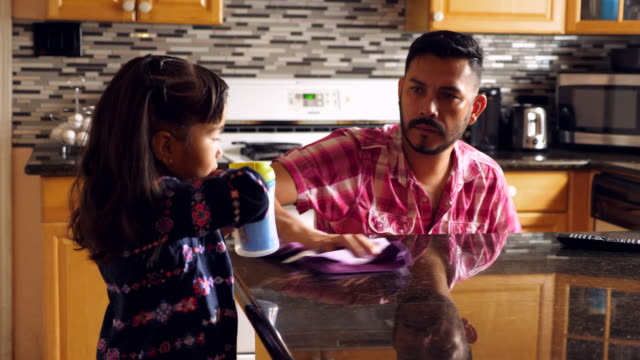 vídeos de stock, filmes e b-roll de ms young girl helping father in wheelchair clean kitchen counter in home - mesa mobília
