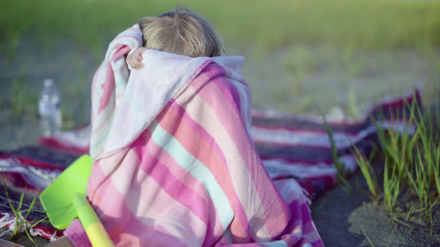 Young girl hides in beach blanket while she sits on the sand in coastal marsh.
