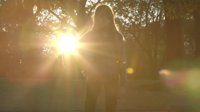 a young girl holding a ball in a park at dusk - endast flickor bildbanksvideor och videomaterial från bakom kulisserna